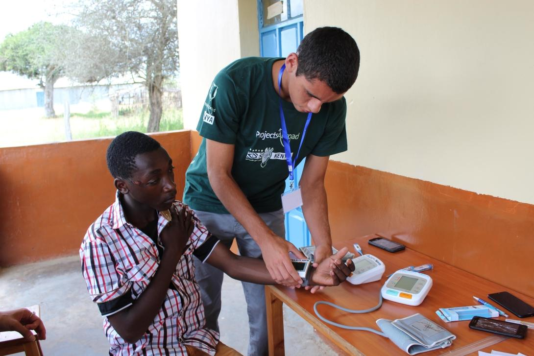 A teenager volunteering in Kenya measures blood pressure levels during a healthcare outreach